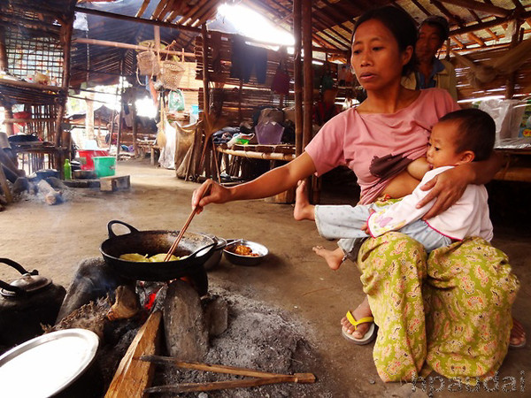 Multitasking at its best: A Kachin mother seen cooking meals for her family while breastfeeding her child.